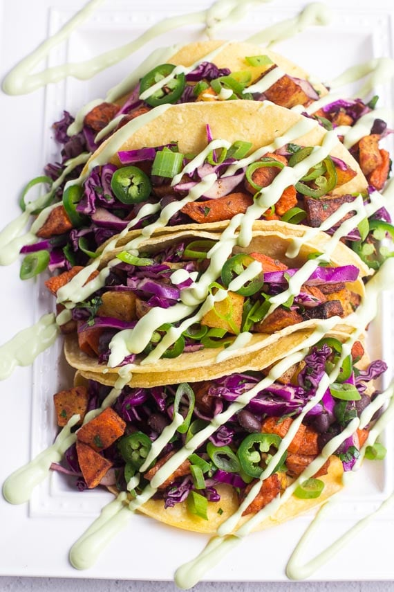 Closeup of low FODMAP sweet potato tacos with black beans and Avocado Lime Crema on white plate