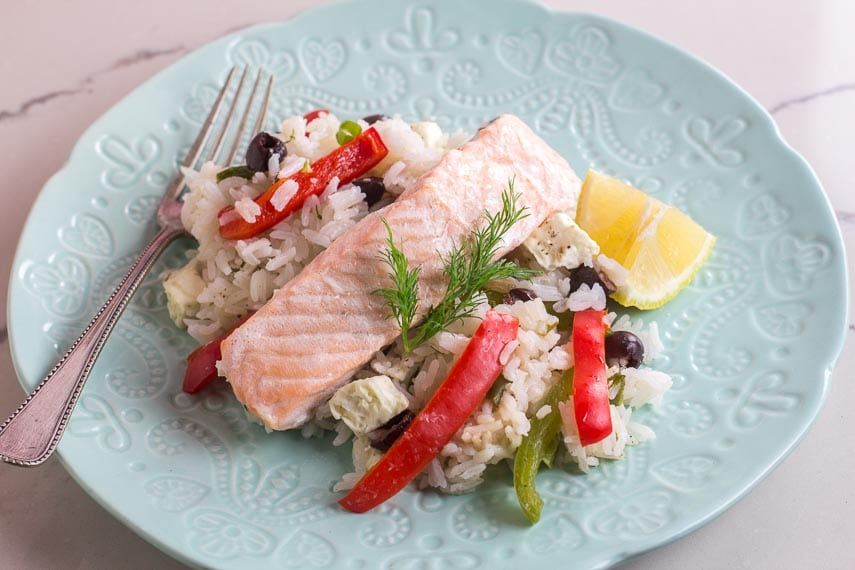 Greek salmon on decorative light blub plate on white quartz with lemon wedge