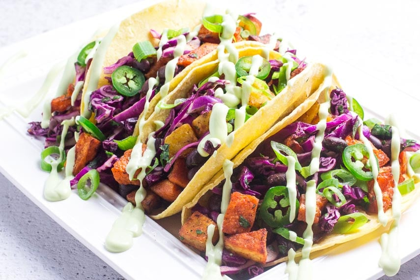 Horizontal image of low FODMAP sweet potato tacos with black beans and Avocado Lime Crema