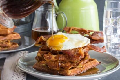 Low FODMAP Cheddar Waffles, stacked, with bacon and egg and maple syrup poured on top, all on a grey plate