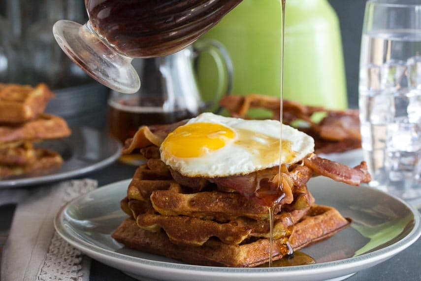 Low FODMAP Cheddar Waffles with bacon and egg and maple syrup poured on top, all on a grey plate