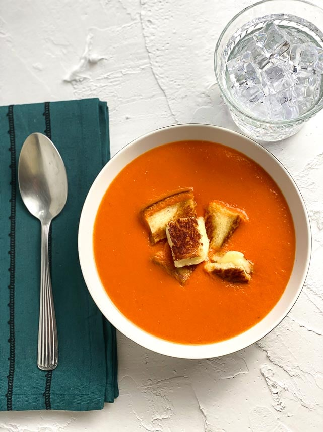 Low FODMAP Cream of Tomato Soup in white bowl; teal napkin