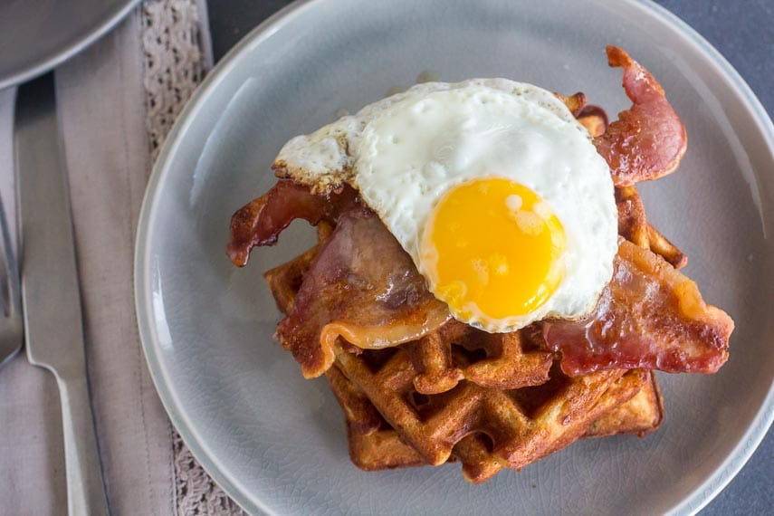 Overhead of Low FODMAP Cheddar Waffles, stacked, with bacon and egg on a grey plate, silverware longside