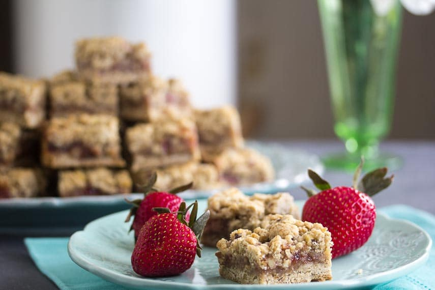 closeup of for Nutty Low FODMAP Strawberry Oat Bars on aqua plate with fresh berries