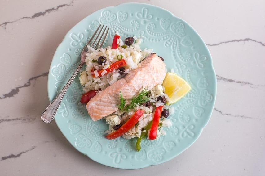 overhead of Greek salmon on decorative light blub plate on white quartz