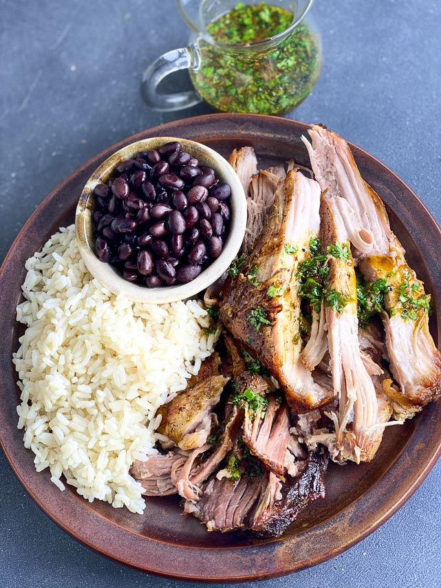 plated Low FODMAP Cuban-Style Roast Pork with rice and beans on brown ceramic plate