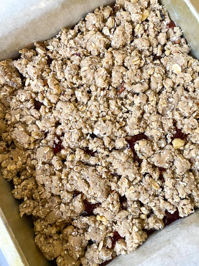sprinkle top layer of dough over jam for Nutty Low FODMAP Strawberry Oat Bars; ready for the oven