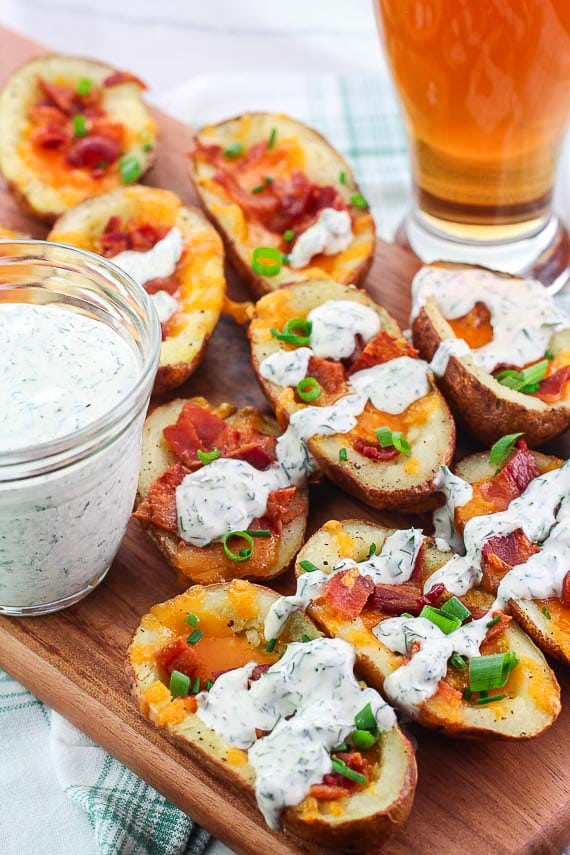 vertical image of low FODMAP stuffed potato skins with melted cheese and Ranch dressing