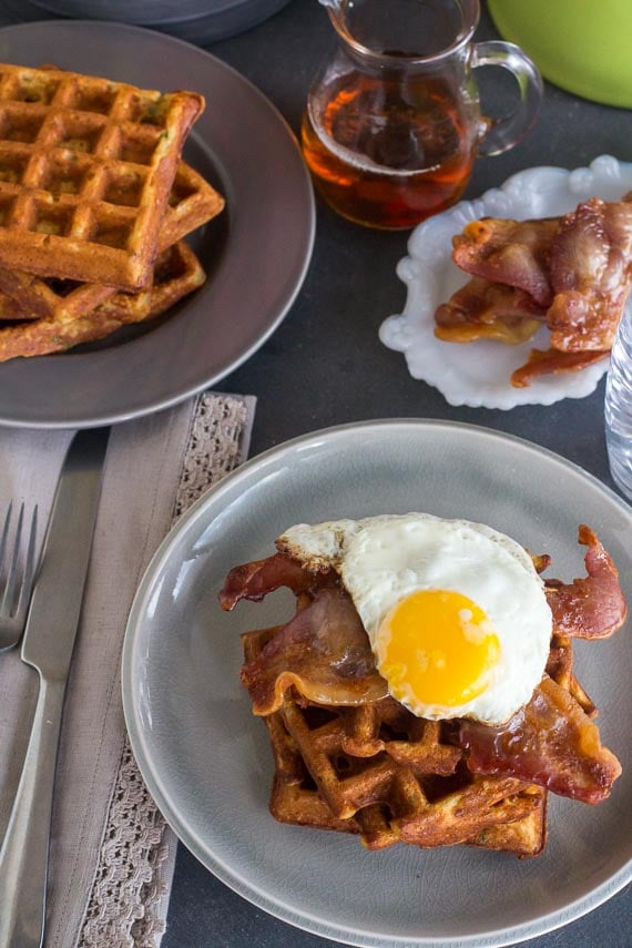 vertical overhead of Low FODMAP Cheddar Waffles, stacked, with bacon and egg on a grey plate