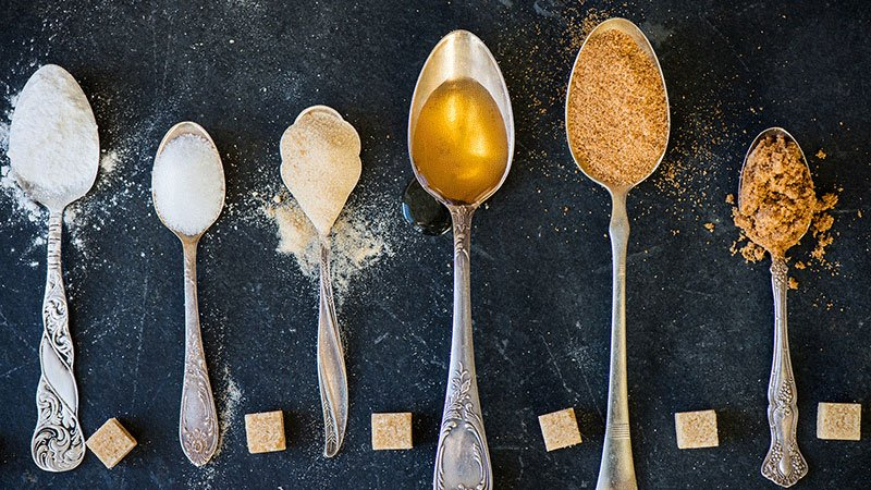 Assorted sweeteners in spoons on dark background