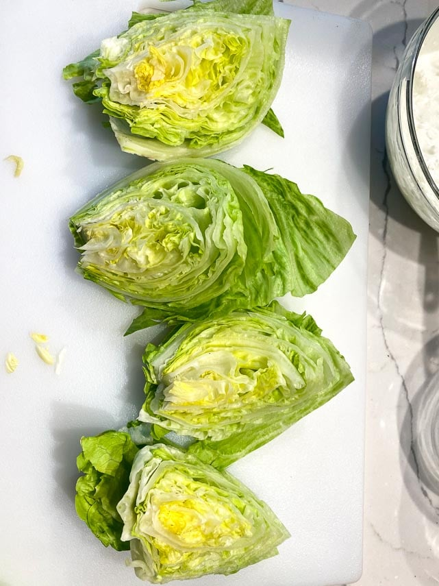 Cutting a head of Iceberg lettuce into quarters on white cutting board