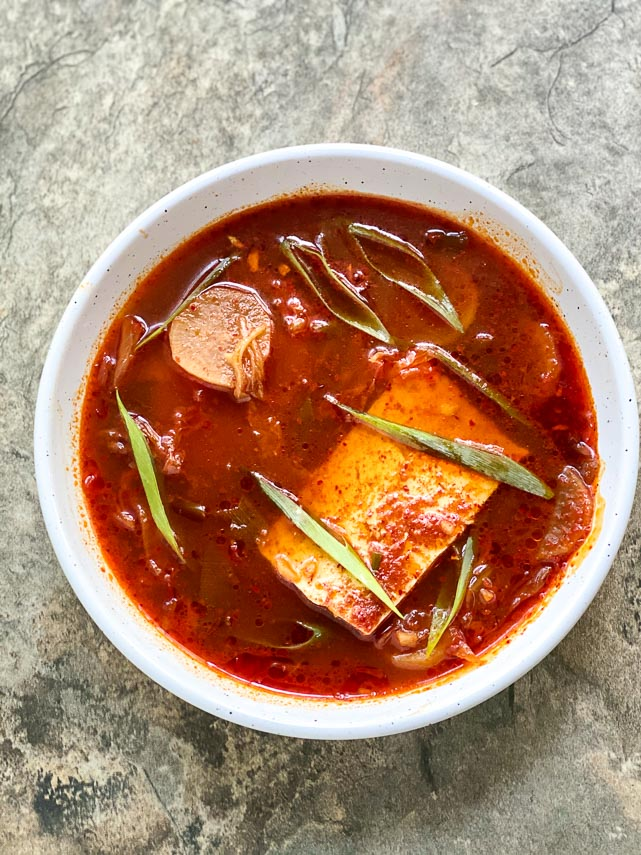 Incendiary low FODMAP Kimchi & Tofu Stew in white bowl on stone surface