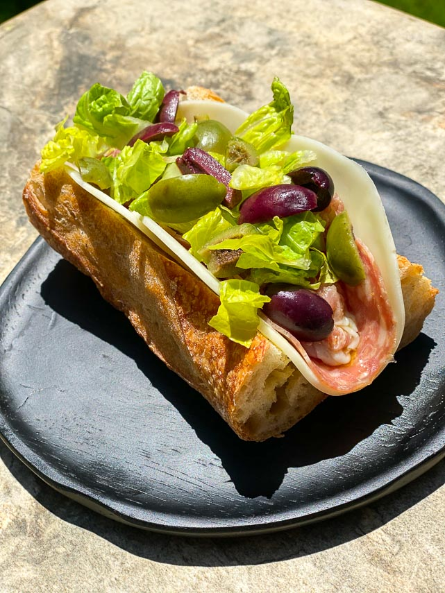 Low FODMAP Italian Sub on a black woode plate, outside on stone surface; heavy shadows across plate