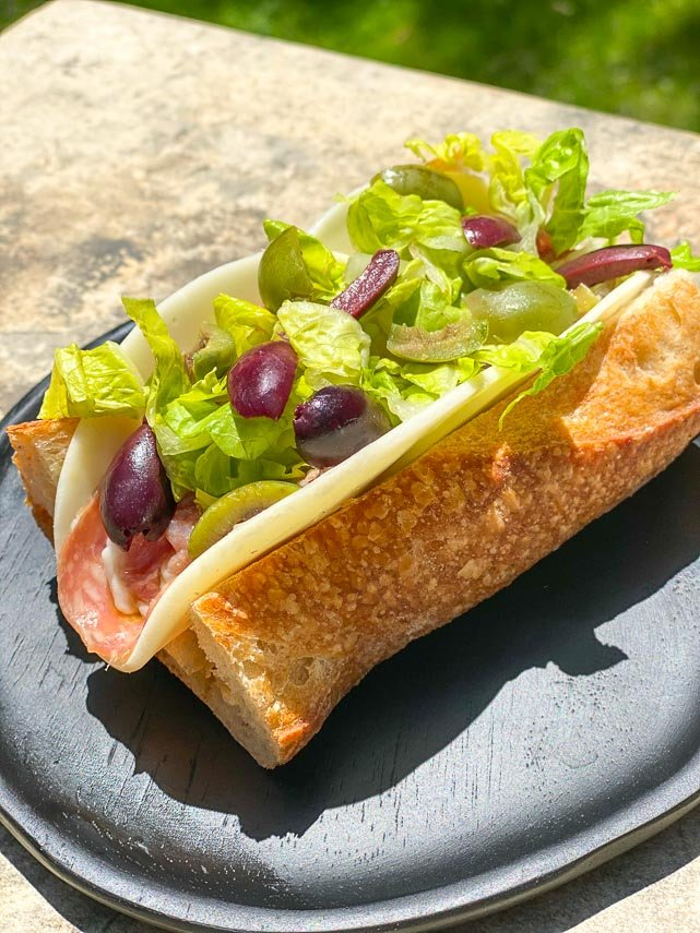 Low FODMAP Italian Sub on a black woode plate, outside on stone surface