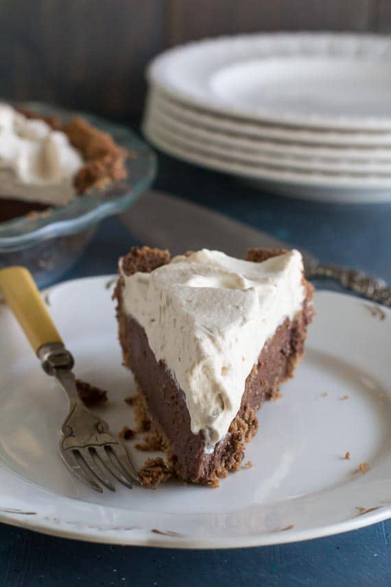 Low FODMAP Black Bottom Pie with Espresso Whipped cream wedge, on a white plate, shot head-on