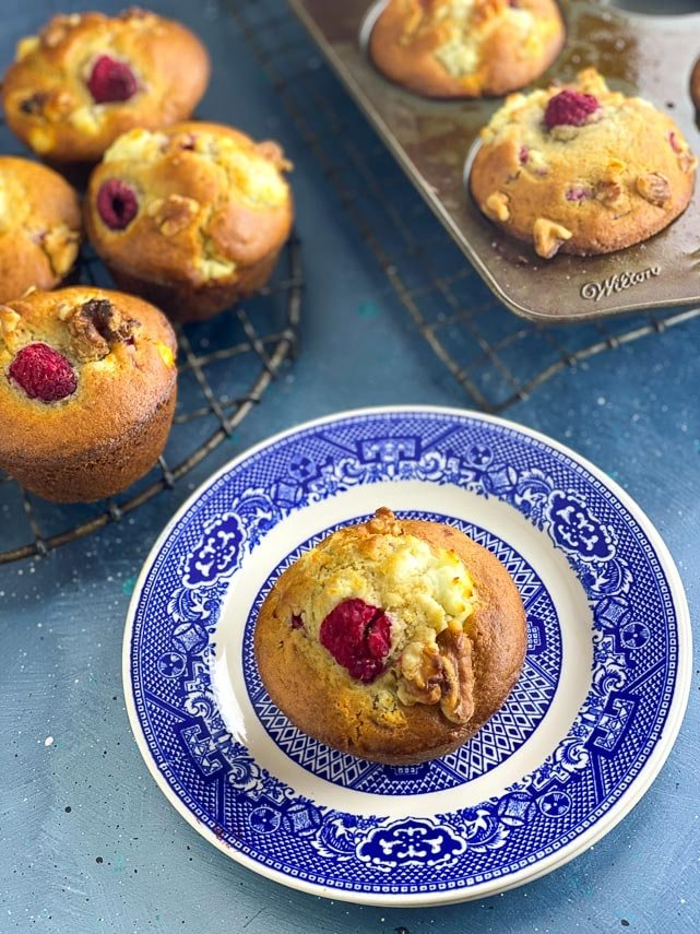 Low FODMAP Olive Oil Muffins with Goat Cheese, Walnuts and Raspberries in a round antique cooling rack; blue backdrop and on blue plate 2