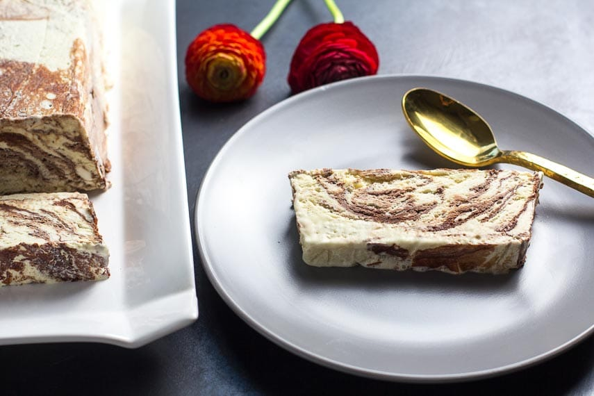 Low FODMAP Semifreddo, slice on gray plate; loaf to the side on white platter with gold spoon