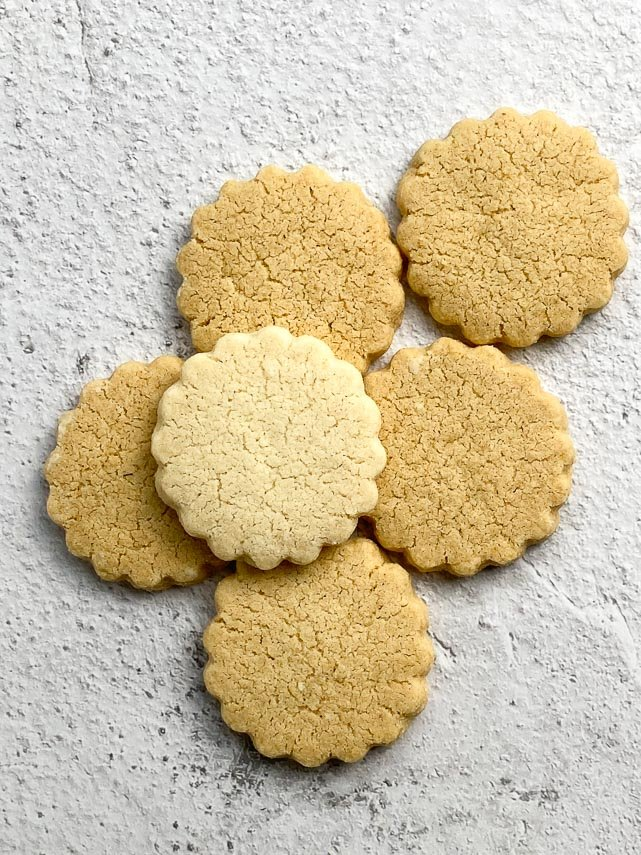 Low FODMAP Shortbread cookies baked to various degrees of doneness against white background