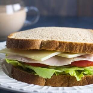 Low FODMAP Turkey & Swiss Sandwich on a white plate; Russian Dressing in background