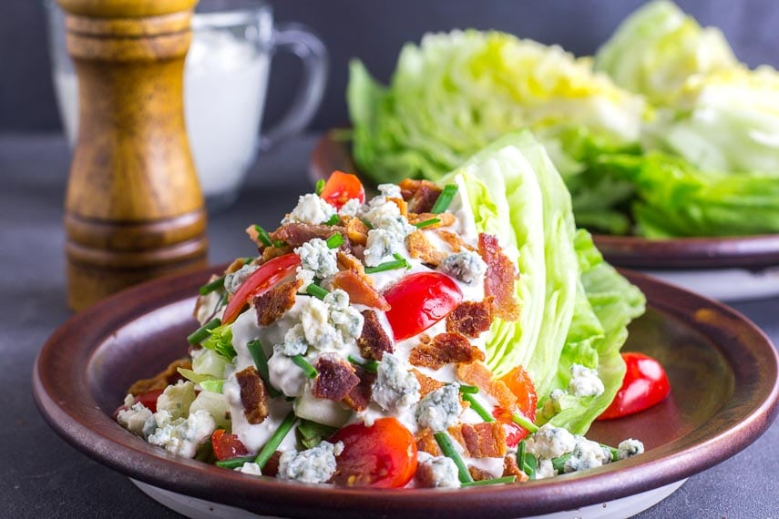 Low FODMAP Wedge Salad slathered with blue cheese dressing on a brown ceramic plate