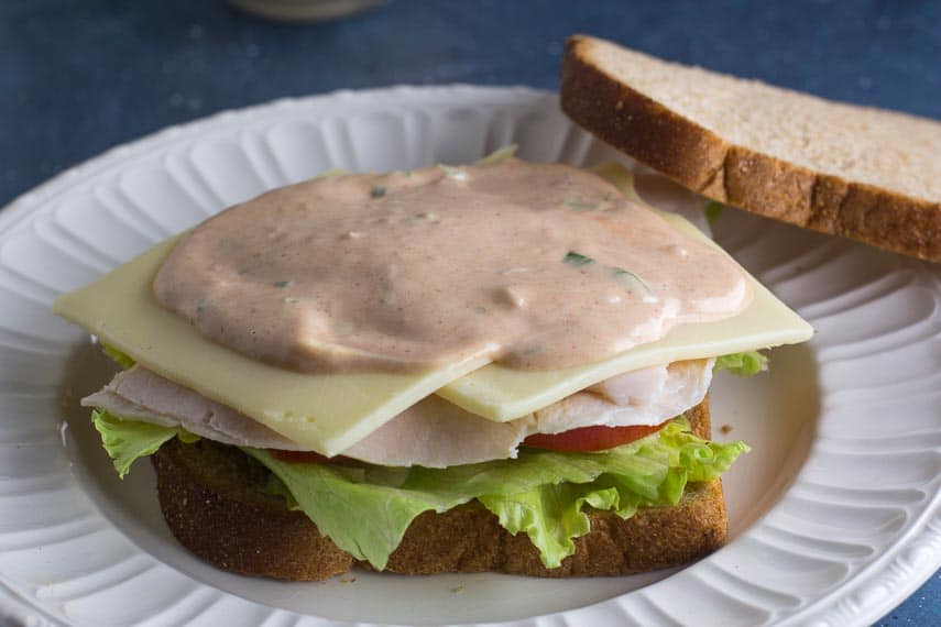 Making a Low FODMAP Turkey & Swiss Sandwich with Russian Dressing; open faced on white plate