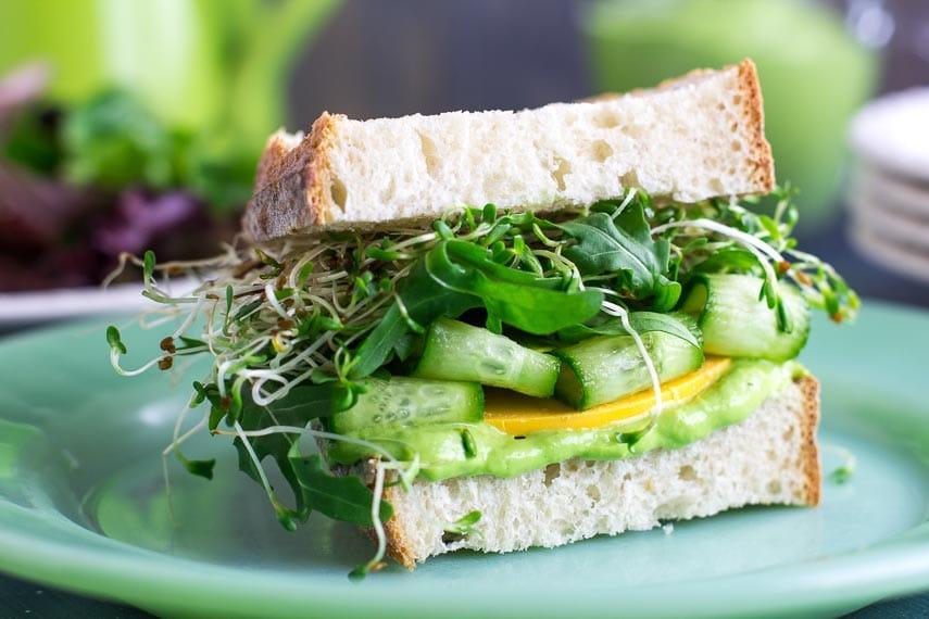 closeup VEGAN Low FODMAP Avocado Green Goddess Veggie Sandwich on green plate