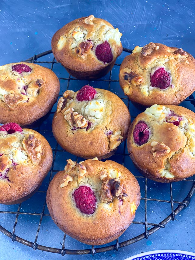 closeup of Low FODMAP Olive Oil Muffins with Goat Cheese, Walnuts and Raspberries in a round antique cooling rack;