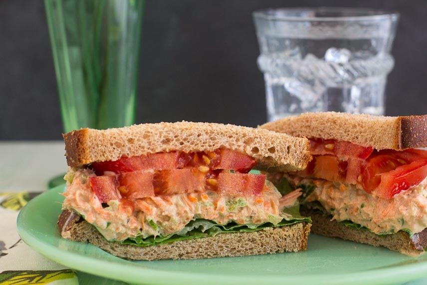 closeup of low FODMAP cajun tuna salad sandwich cut open on green plate