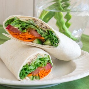 closeup of low FODMAP hummus wrap on white plate; green napkin