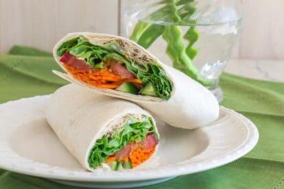 closeup of low FODMAP hummus wrap on white plate; green napkin