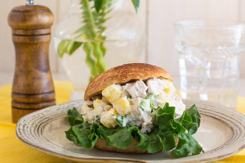 closeup shot of Low FODMAP Pineapple Chicken Salad on a roll with lettuce; peppermill and glass of water in background