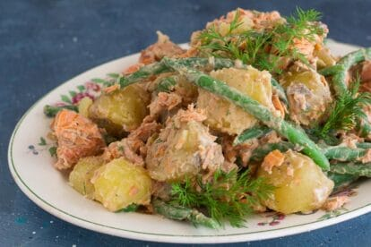 horizontal image of low FODMAP Salmon Potato Salad with green beans and dill sprigs on white oval platter; blue background