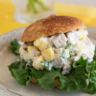 low FODMAP Pineapple Chicken salad on a roll with yellow napkin in background