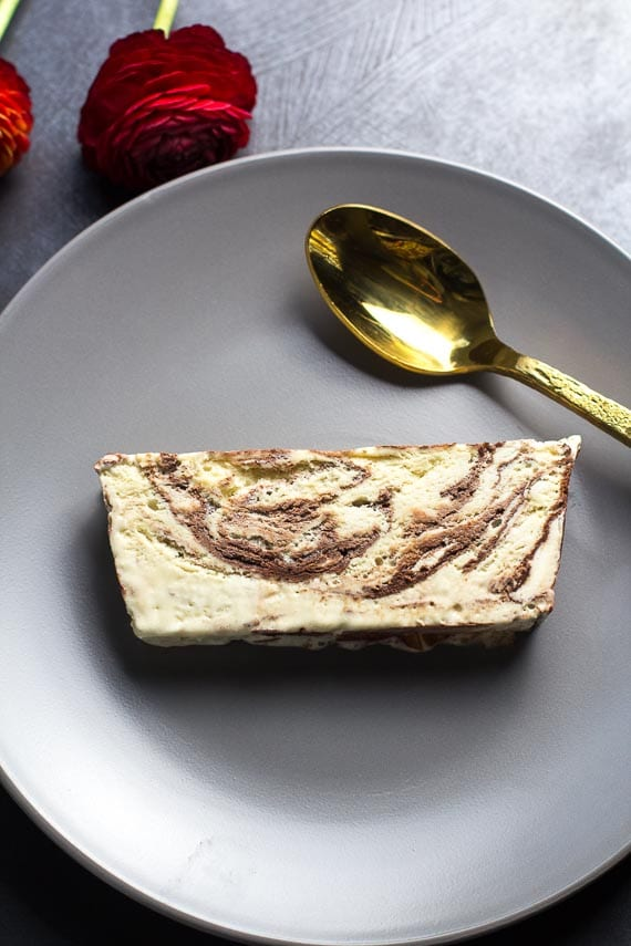 low FODMAP semifreddo slice on a plate with gold spoon, gray backdrop