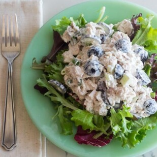 overhead horizontal image of Low FODMAP Chicken Salad with Grapes and Almonds on a bed of lettuce on a green plate; fork and linen napkin alongside