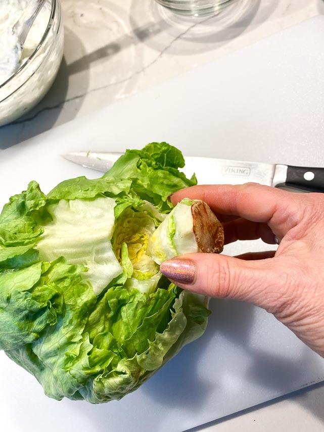 removing core of iceberg lettuce for making wedge salad