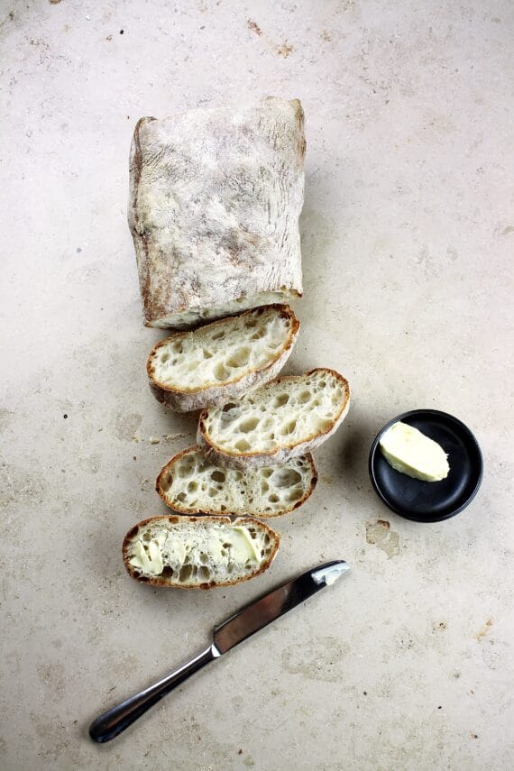 loaf of artisan bread on light background, sliced