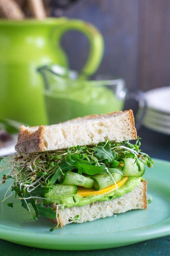vertical image VEGAN Low FODMAP Avocado Green Goddess Veggie Sandwich on green plate
