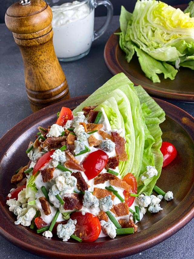 vertical image of Loaded Low FODMAP Wedge Salad sprinkled with bacon, blue cheese, tomatoes and chives on brown ceramic plate; peppermill in background