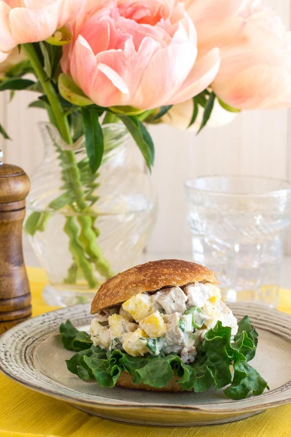 vertical image of Low FODMAP Pineapple Chicken Salad on a roll; pink peonies in background