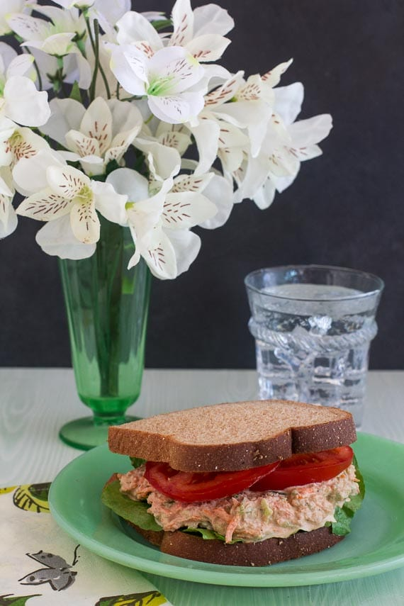 vertical image of low FODMAP cajun tuna salad sandwich on green plate; glass of water