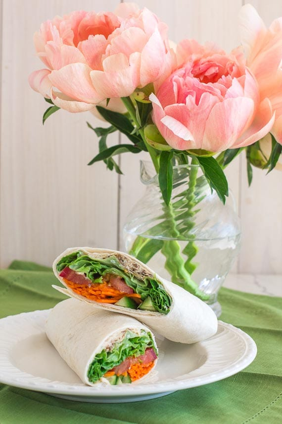 vertical low FODMAP hummus wrap on white plate with peonies in background