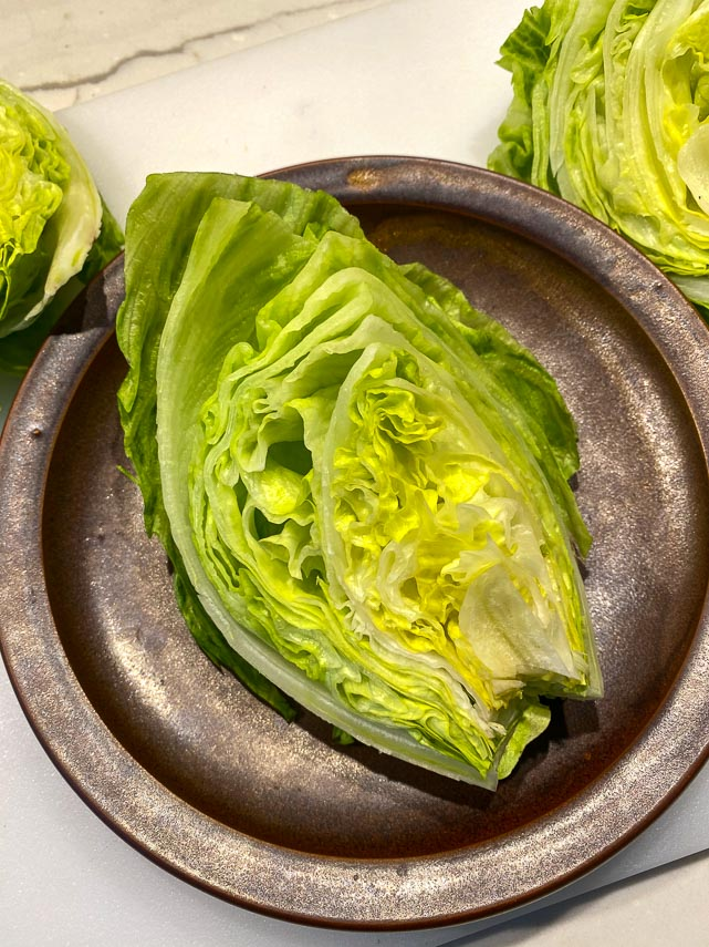 wedge of Iceberg lettuce on a brown ceramic plate