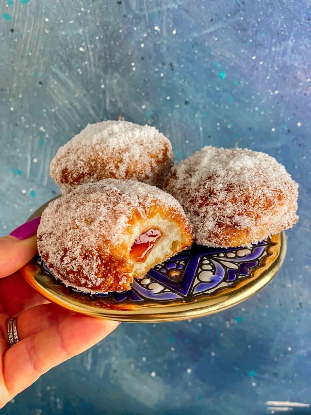 3 low FODMAP jelly donuts on a blue plate, held in hand