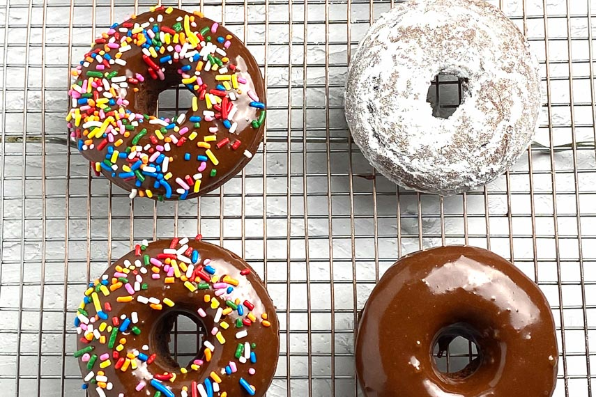 4 Low FODMAP baked Chocolate Doughnuts with various toppings on rack