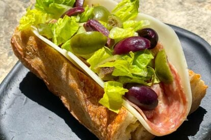 CLOSEUP Low FODMAP Italian Sub on a black woode plate, outside on stone surface; heavy shadows across plate
