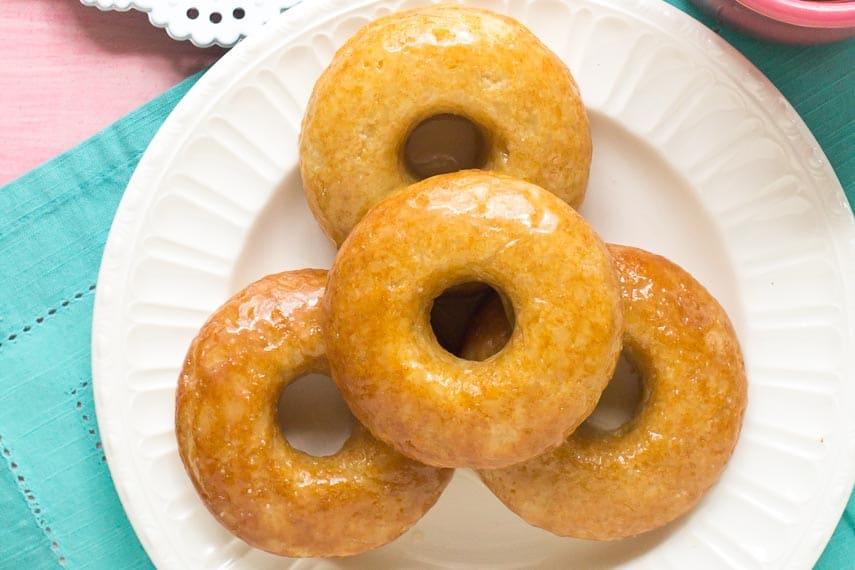 Honey Glazed Low FODMAP Doughnuts piled on a white plate with aqua napkin