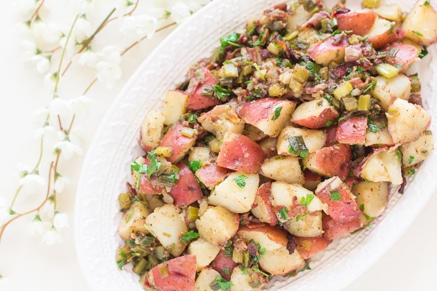 Low FODMAP Hot Potato Salad with bacon on decorative oval white platter