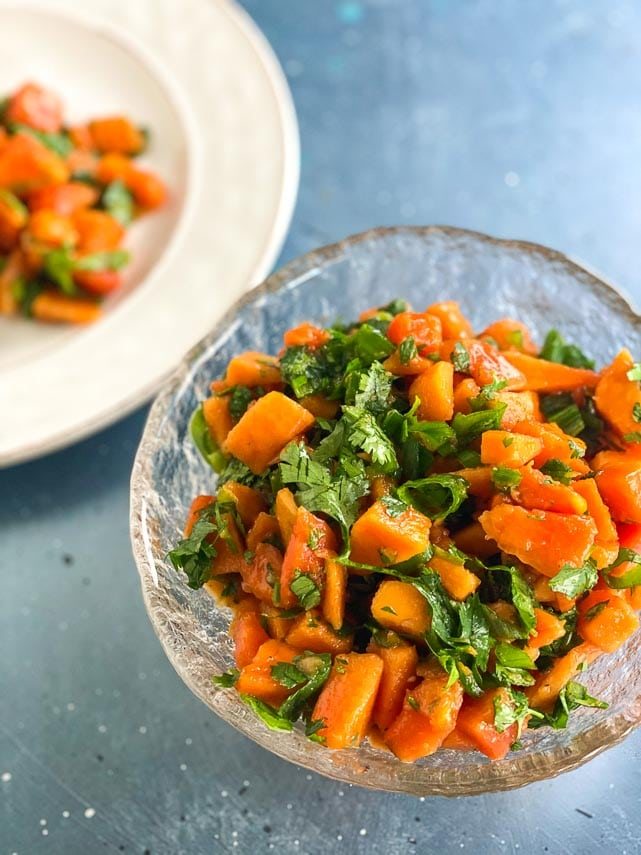 Low FODMAP Papaya Salsa in clear bowl in blue surface; vertical image