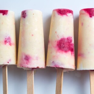 Low FODMAP peaches & cream popsicles with raspberries, close up, lined up on white plate_